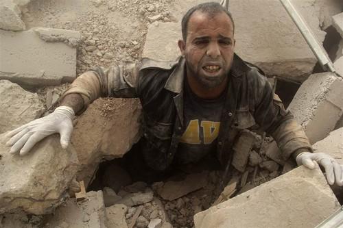 De acordo com a Reuters, esta sua foto mostra um membro dos White Helmets preso em destroços causados por um bombardeamento do governo sobre Aleppo no dia 27.07.2014